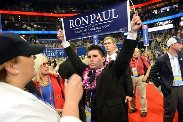 A security agent calls for more security as delegate from Virginia Braedon Wilkerson displays a Ron Paul sign after the vote on Maine at the Tampa Bay Times Forum in Tampa, Florida, on August 28, 2012 during the Republican National Convention. The 2012 Republican National Convention is expected to host 2,286 delegates and 2,125 alternate delegates from all 50 states, the District of Columbia and five territories. AFP PHOTO Robyn BECK (Photo credit should read ROBYN BECK/AFP/GettyImages)
